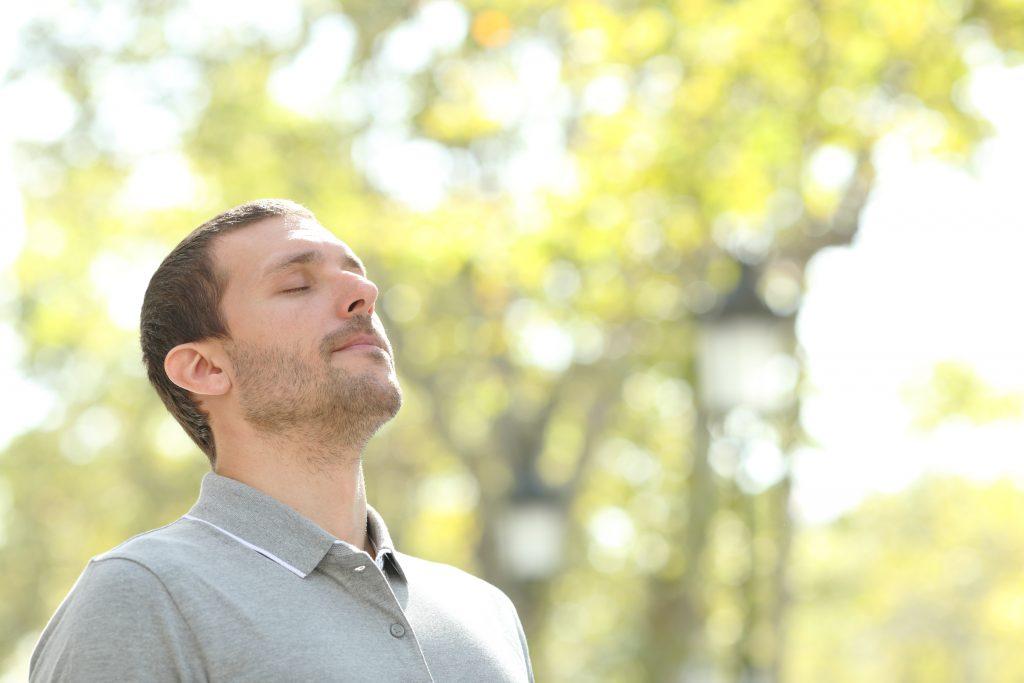 homme qui respire à pleins poumons serein grâce à l'hypnose