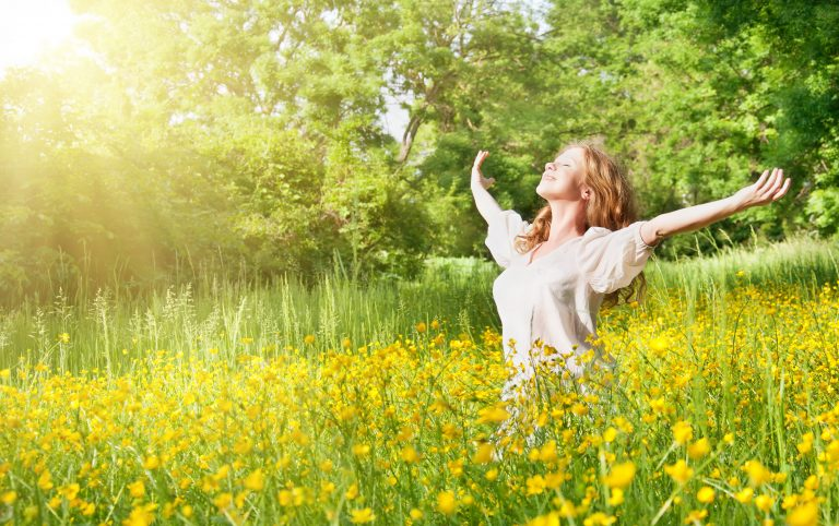 Femme qui ouvre grand les bras dans un champs plein de fleurs grâce à l'hypnose